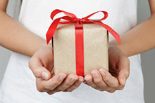 A woman holding a gift wrapped with a red ribbon.