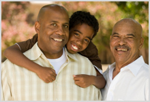A grandfather, father, and son smiling.