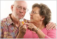 Senior couple reading a label on a prescription bottle.