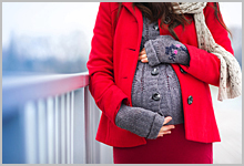 A pregnant woman clutching her stomach during winter.