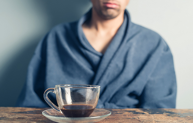 A tired man drinking coffee.