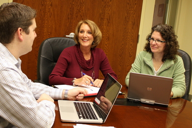 Inforia, Inc. President Karen Goetz (center) meets with employees Ryan Long and Jennifer Pitt