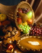 cornucopia full of fruit and a pumpkin pie