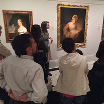 Group listening to an educator in front of a portrait