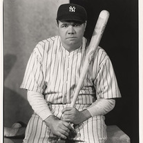Babe Ruth sitting with a baseball bat