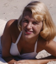 A blonde woman in a white bathing suit on the beach