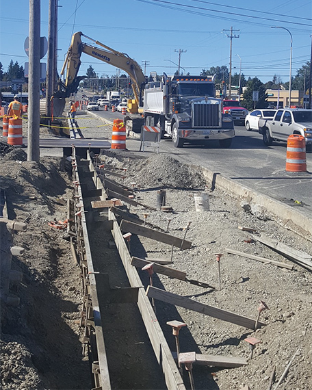 Construction crews are backfilling dirt on what will be a new sidewalk along the south side of 128th Street just west of I-5.