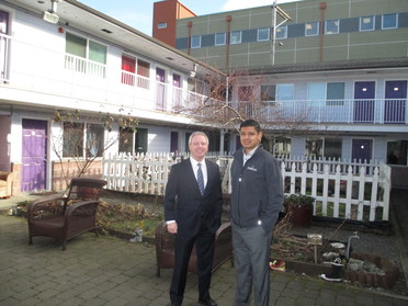 Terry and Julio Cortes in the courtyard of a Cocoon House housing complex in Everett.  Behind them is the garden area where residents grow their own v