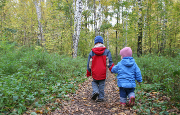 Young kids walking through the woods, bundled against the cold.