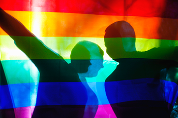Two silhouetted people holding up a LGBTQ Pride Flag