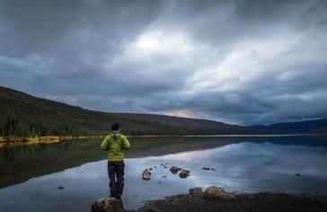 Man stands on a rock on an Alaska beach at sunrise