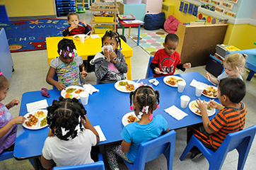 Preschool kids sit at their lunch tables enjoying health food.