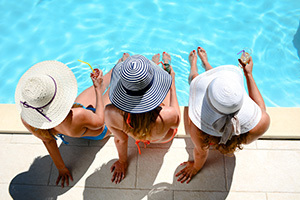 Women by pool with hats