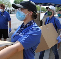 Volunteers in line with boxes of PPE
