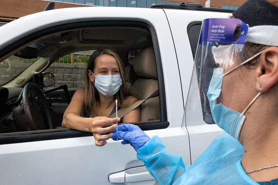 woman in a white truck doing a drive thru covid 19 nasal swab test, medical personnel in personal protective equipment