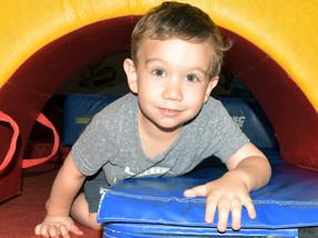 Little boy climbing through obstacle