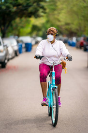 Woman riding a bike at a relaxed pace, wearing a mask.