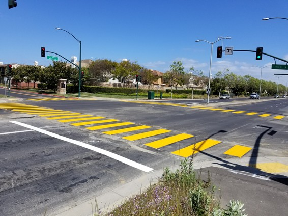 Freshly painted high visibility crosswalk across four-lane road with traffic signals