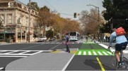 Rendered image of a future road with pedestrian islands, bus stop, and two-way protected bike lane