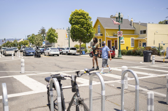Two people cross Park St in a crosswalk, with bollards and bike racks visible, and cars stopped for them.