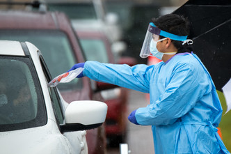person handing test kit to person in car at mobile COVID-19 testing site