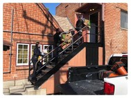 three Culver City Police Department members deliver boxes of food up stairs