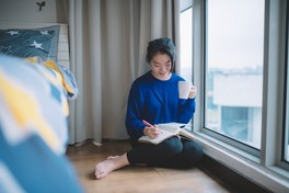 woman indoors sitting near window while writing in journal
