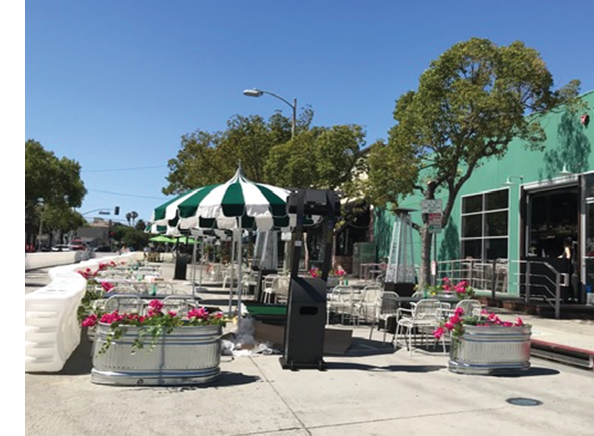 Street Scene in Downtown Culver City. Socially distanced tables and flowers in street.