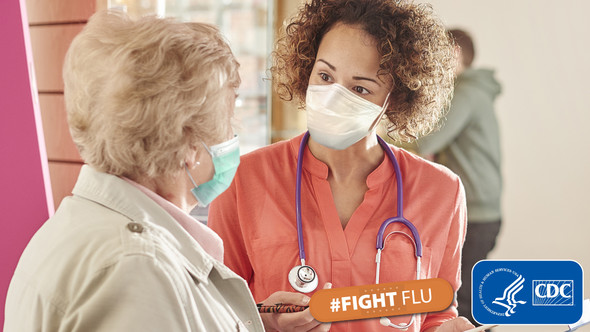 doctor in scrubs talking with a patient. Both are wearing a mask. #FightFlu CDC