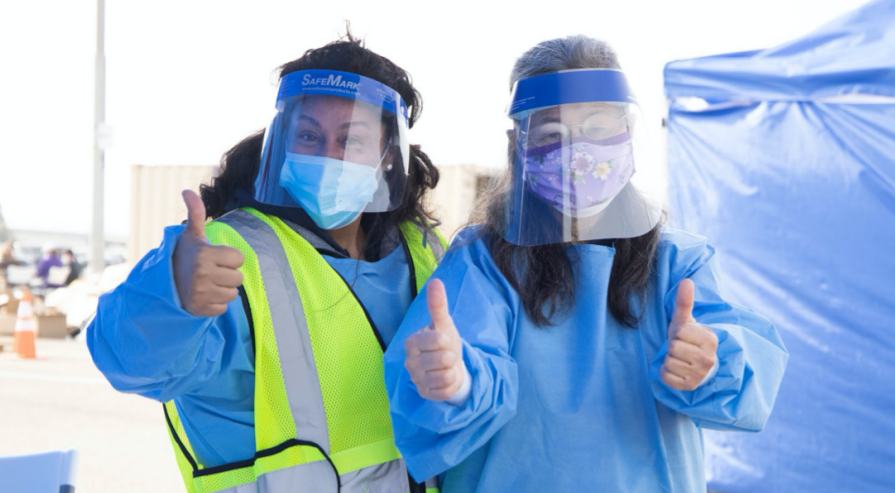 Photo of two Healthcare workers in PPE giving two thumbs up