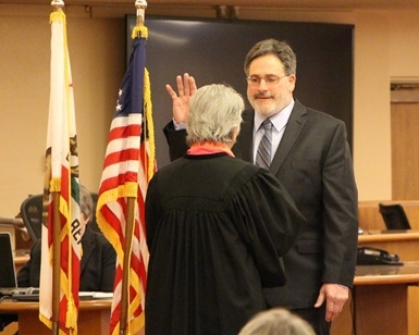 Dennis Rodoni raises his right hand and takes the oath of office from Judge Faye D'Opal