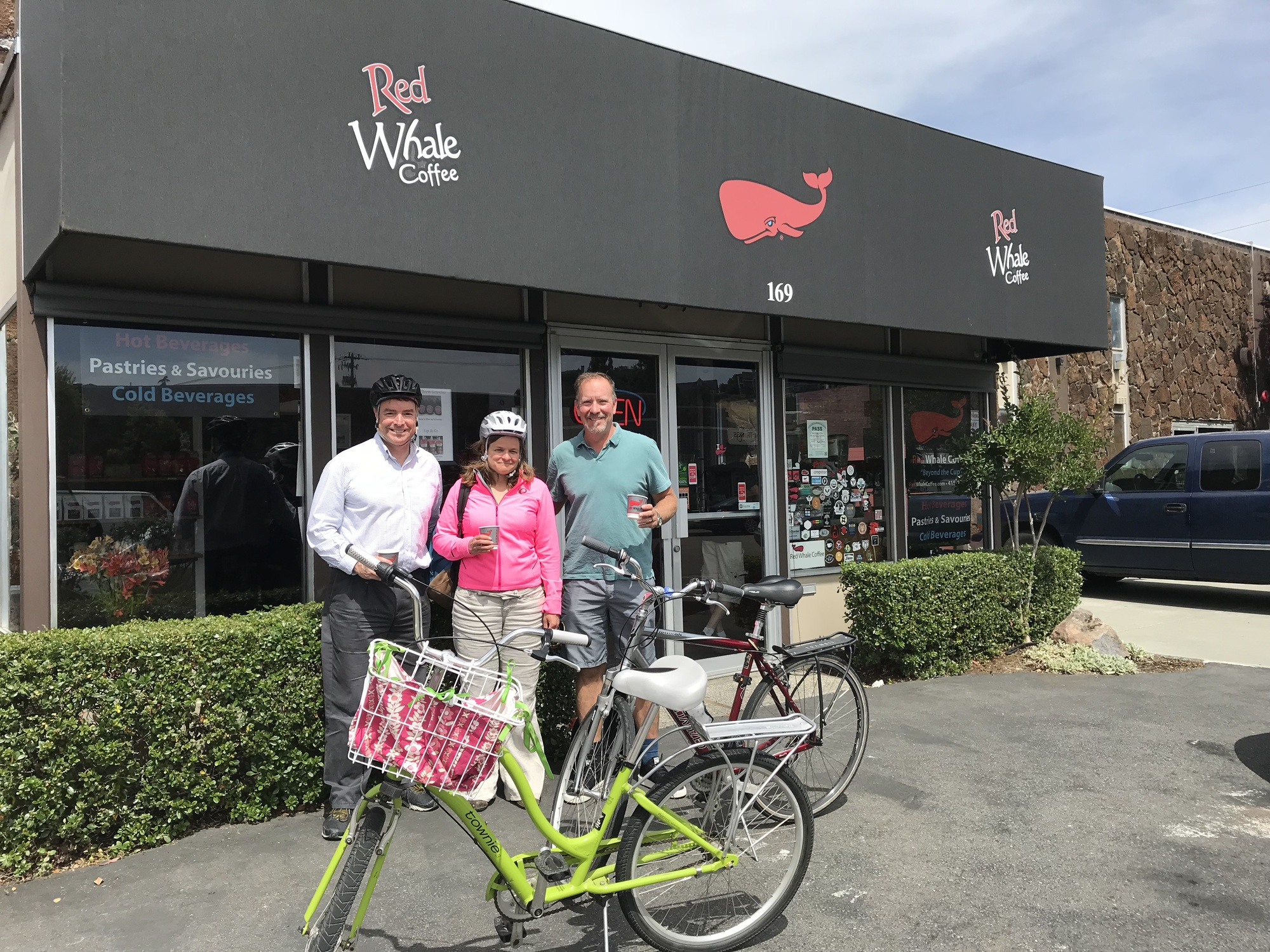 Supervsor Connolly, Connolly's Aide Mary Sackett, and Sean Boyd owner of Red Whale Coffee in front of Red Whale Coffee with bikes