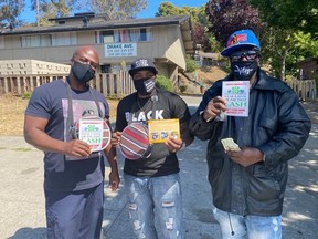 3 men wear cloth face masks and hold up signs about face coverings being required