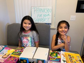 2 kids show off their art and reading supplies and a sign in the background says thank you