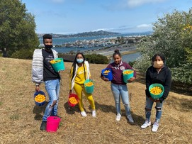 4 young people hold buckets of produce from the garden