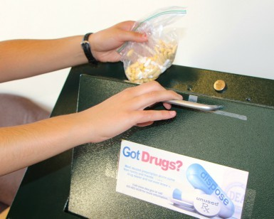 A hand holds a bag of prescription medicine, while another hand opens a safe disposal box.