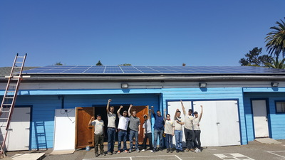 Volunteers at Harbor House celebrate their new solar panels