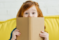 Young girl smiling from behind a book