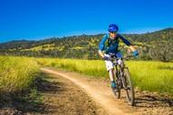 Cyclist ride a trail through hilly, green terrain