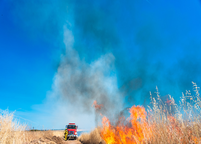 Fire Truck driving up to a wildfire in a field