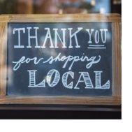 """In the window of a business sits a chalkboard sign that reads """"thank you for shopping local."""""""