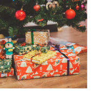 An assortment of gifts wrapped in brightly colored paper sit on a wood floor under a tree adorned with red ornaments.