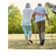 A woman holds a man steady as he walks with forearm crutches through a park.