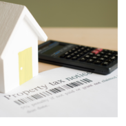 A small paper house and a calculator sitting on a property tax notice.