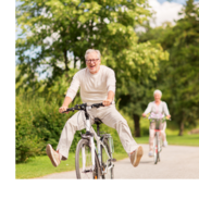 An older man, happily riding a bike, lifts his feet off the petals to coast. An older woman follows him on a bike.