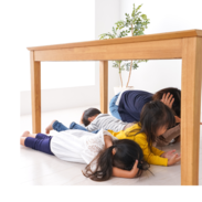 Four children practice covering their heads under a wooden table during an earthquake drill.