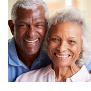 An older couple smile and pose together. The man has his arms around the woman.