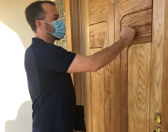 A social worker holding a clipboard and wearing a mask knocks on a door.