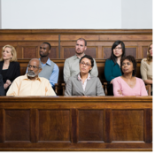 A diverse group of jurors sit in a jury box and listen to arguments in an ongoing case.