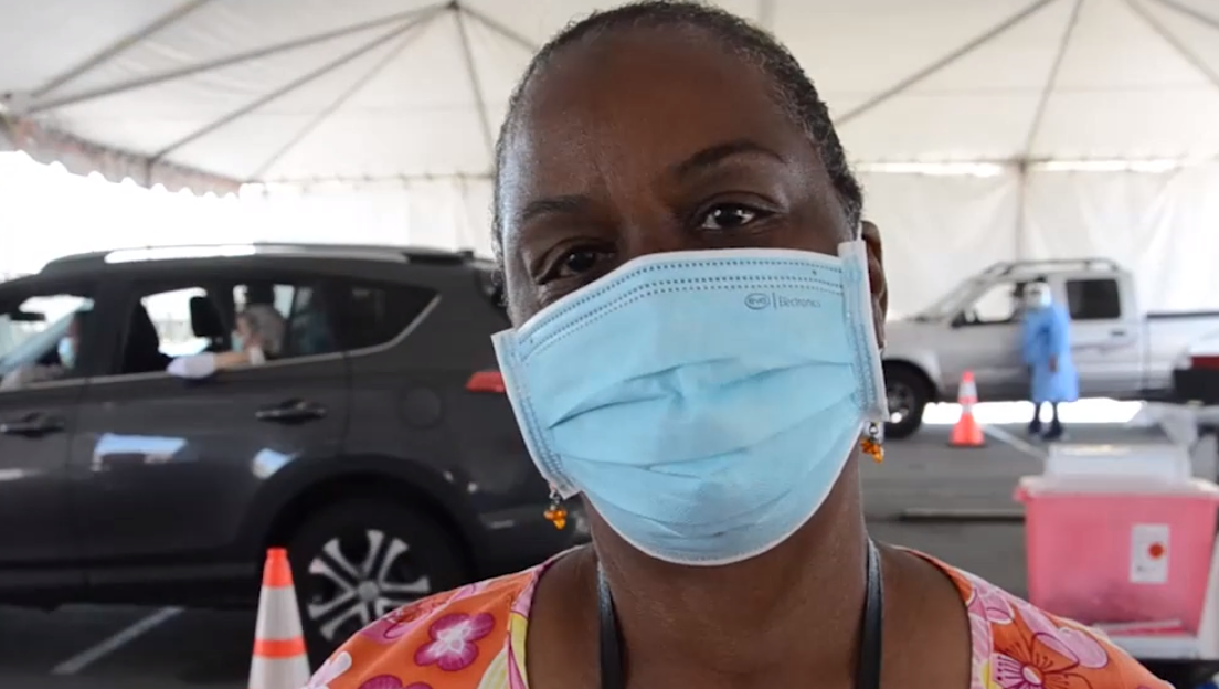 A woman wearing a face mask stands in a tent. There are cars and medical supplies behind her.